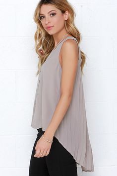 """The Joy to the Whirled Taupe Top isn't just happiness inducing, it's love at first sight! This lightweight Georgette top has a sleeveless bodice and rounded neckline above a billowy swing bodice. Neckline fastens above a cute keyhole at back before trailing down in a pleated back, ending in a rounded, high-low hem. Front of bodice is lined. Top measures 6"""" longer at back. 100% Polyester. Hand Wash Cold."""