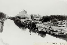 "Caption: ""Black and white photograph looking across the canal, in the foreground is a barge with ""Odell"" written on the bow. Next to the barge is a ""Grand Junction Canal Company, Bulbourne."" narrowboat with a steam engine in the hold. The wharf construction (for Hayes Develoment company) is visible in the background with numerous workers present. In the distance there are industrial buildings and a steamer on the canal."""