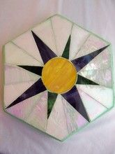 This is a hexigon shaped stepping stone with a starburst pattern which is 12 in.  It is a cement stone set with iridescent glass.