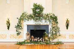 fireplace mantle decorated with candles and greenery