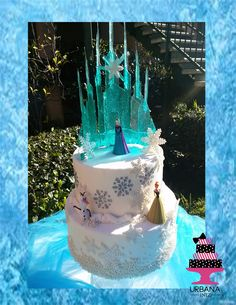 Elsa's Castle.  2 tiered cake with Isomalt cake topper.  The spires reach 8 inches in height.   Also available with lights for your indoor parties.   www.urbanainez.com