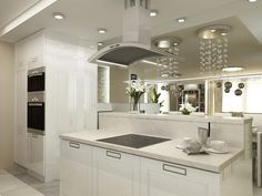 This sleek white kitchen looks out into the dining room and living room beyond, making it perfect for entertaining guests. The electric stovetop blends seamlessly into the counter and even the ventilation hood doesn't take away from the overall polished feel of the room.
