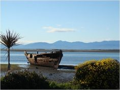 Motueka - New Zealand   The beach, and the wreck of the Janie Seddon. Nelson is nestled into the mountains across the Tasman Bay