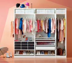 Eine weisse PAX Kleiderschrankkombination ohne Türen, in der bunte Kleidung hängt und Schuhe und Hüte und viele kleine Boxen untergebracht sind