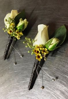 Small groomsmen's boutonnieres of rose, spray rose, yellow wax flower and seeded eucalyptus by Seasonal Celebrations, http://www.seasonalcelebrations.com