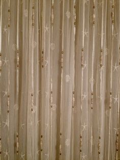 Heritage Lace Sand Shell curtain panel with ribbon & bead curtain hung in front.  Creative!