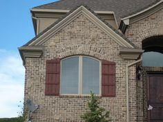 """Board and batten shutters on a magnificent home. The sweep cut across the top lends a little line deviation  to the facade which showcases crown molding and soffit lights. The coloring job is what we call """"smoking"""", where just enough darker color is added in the shadows and edges. A great look."""