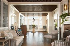 The entrance hall boasts two glass trophy cases. Under one sits a plush Palecek sofa upholstered in Holland & Sherry fabric, which faces a fireplace from the original building. In the distance, at the entrance to the dining room, is an antique mahogany host stand.