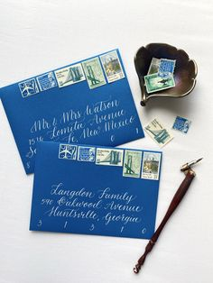 Hand lettered, traditional pen and ink calligraphy. White ink on blue envelopes. Vintage postage by @littlepostagehouse