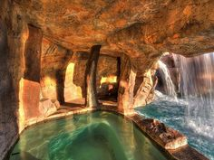 Cave-Like Spa Behind Waterfall Surrounded by Stone-Walled Grotto