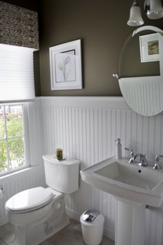 High contrast powder room.  Dark walls, white beadboard wainscot, pedestal sink, pleated shades and fabric cornice, stone tile floor.  Round mirror and wall sconces. Classic New England with a Victorian cottage beadboard detail.