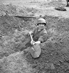Sgt. Al Grayston, Canadian Film and Photo Unit, digging a trench, Normandy, France, 10 June 1944.