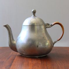 Dutch pewter tea pot with a rattan-wrapped handle.