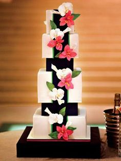 Modern Cake Sugar paste lilies and orchids top a four-tiered square cake -- my favorite part? The jet-black columns that section off each layer of the cake, giving it a modern look. (Made by Custom Cakes in Savannah, GA)