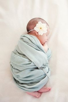 Sweet baby picture. Blanketed, foots showing with a big flower <3