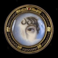 An early 19th century gold mounted 'eye' brooch The circular brooch centred with ... a painted miniature of a lady's eye, with curls of hair on her forehead, the border modelled out of hair and gold as an ouroboros, symbol of eternal life.