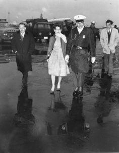 A U.S. military policeman escorts Priscilla Beaulieu, 16, after she broke through a barrier trying to bid her boyfriend Elvis Presley goodbye at Rhine-Main airbase in Frankfurt/Main, Germany, on March 2, 1960.