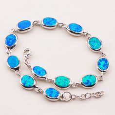 Striking oval cut fire opal stones linked on this bracelet. This bracelet will add extra beauty to your ensemble. Comes in blue or white. BRACELET DETAILS - Length: 7.5 in. - Clasp: lobster-claw - Met