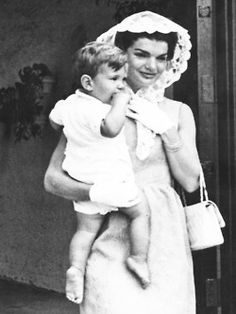 Jackie Kennedy, wife of President Kennedy, wears a white lace mantilla, while John F. Kennedy Jr. goes without shoes, as they leave the home of the President's father, where the first family attended a private family mass in the morning.