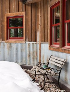 """Reclaimed corrugated metal makes """"totally bomb proof"""" exterior wainscoting that helps protect the lower part of the house from roof runoff.:"""