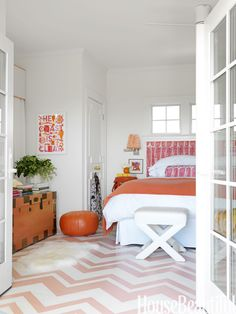 """""""The master bedroom has a very retro feel to it,"""" says designer Mona Ross Berman, """"with the pink, tangerine, and lavender color palette, the paisley linen, and the zigzag Missoni-esque pattern on the floor."""" The floor is painted Salmon Berry and White Dove, both by  Benjamin Moore. The headboard is upholstered in Henry in Rose by Raoul Textiles. Pouf from  John Derian.   - HouseBeautiful.com"""