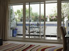 View through open sliding glass door to table and chairs on balcony