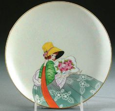 A NORITAKE ART DECO PORTRAIT PLATE CIRCA 1925, WITH PAINTED SCENE OF A WOMAN WITH BOUQUET ON MOTHER-OF-PEARL GROUND