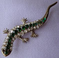 This fabulous brooch probably dates circa 1920. It is in the form of a crawling lizard and is adorned with shimmering claw-set diamante and emerald green faceted glass stones.