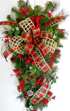 24 inch teardrop evergreen swag. Open weave natural ribbon with red/green plaid ribbon with bell in center. Red berries, berry pics, pine cones, mistletoe and honeysuckle vine