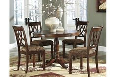 Details Round tables encourage conversation, and more so when it centers around the Leahlyn dining table set. The exquisite tabletop is strikingly patterned with diagonal grains flaring out from the center. Classic pedestal base is beautifully supportive. Pierced splat back chairs are comfortably cushioned and upholstered with a subtle floral, earth-tone fabric.