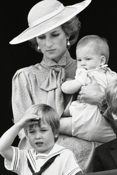 June 1985: Prince William makes a salute as he watches the Trooping the Colour from the balcony of Buckingham Palace with his brother Harry and mother Princess Diana