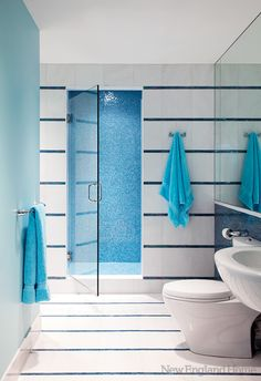 Strips of iridescent glass tile shimmer against white granite in the bathroom. look closely this is some amazing design