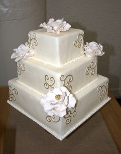 White floral cake coated with fondant, decorated with gilded scrolls.