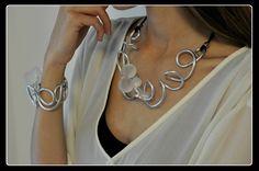 Collana realizzata in filo di alluminio argentato e bellissime perle bianche di resina effetto vetro satinato (made in Italy)  Il contrasto del luminoso alluminio con le perle opache bianche, rendono questa collana particolarmente elegante, pur di aspetto contemporaneo.  Con un cordino bianco sarà