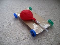 How to make an air powered balloon car. All you need are bottle tops, 2 pens, a hammer, a nail, some carboard and a balloon