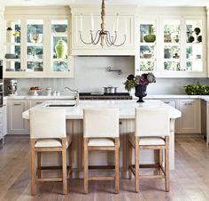 Windows form the back of these glass-front kitchen cabinets, affording views of silver vases and colorful pottery from the inside and outside. The extra windows also allow sunlight to flood the kitchen through an unconventional source.