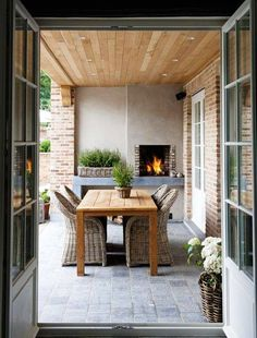 beautiful outdoor dining area with slate flooring, light wood ceiling, and fireplace