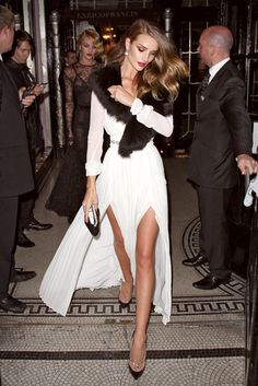 sheer cream evening dress with knife-pleated, double-slit skirt and asymmetrically worn, dark faux fur stole.
