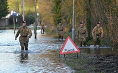 Soldiers from1 Royal Regiment of Fusiliers wading through floodwater in Staines-upon-Thames, Surrey.
