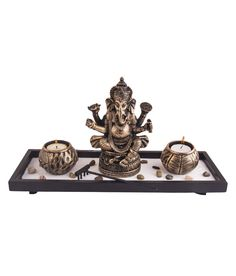 A beautiful and divine piece; this is a perfect addition to your home this season. It is a Bhakti Ganesha statue placed on a rectangular tray with copper oxidised finish, and flanked with two round inlay tea light holders.