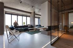 The open floorplan in this industrial loft space is no surprise, but the creative way the different rooms and sections are divided is certainly unique. Interior glass paneling acts as an open division, so that light from the sweeping wall of windows is never far behind, yet there is some separation between bed and bath, living and sleeping.