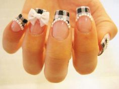 An adorable plaid French tip design. The colors are a combination of a white base topped with black and gray stripes to fill the nail tip. Additional white beads and ribbons are paced for a cuter effect.