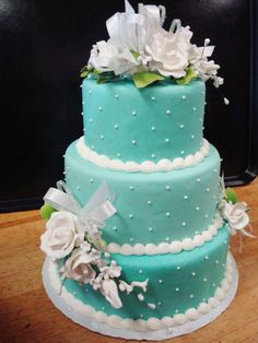 An aqua #cake designed by Tiffany's Bakery. Gorgeous pearl and flower details really bring this 3-tier wedding cake together.
