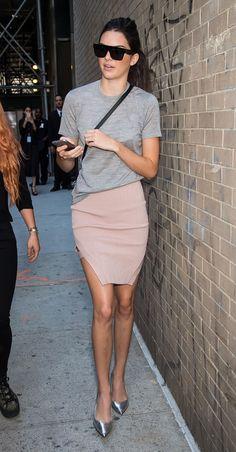 Kendall Jenner wears a gray t-shirt, blush pink miniskirt, metallic heels, rectangular sunglasses, and a crossbody bag