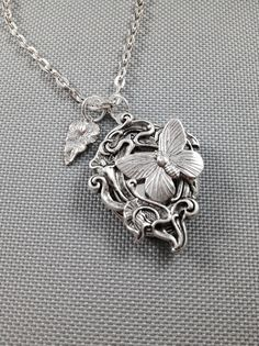 A beautiful butterfly locket with a antique silver frame attached to locket.  Chain 24 inches Locket 34 x 24mm  Locket does open and holds photos.