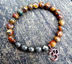 This unique bracelet was made of natural multi-colored picasso jasper, faceted pyrite, copper OM and beads. It brings calmness, peace and helps to release stress.