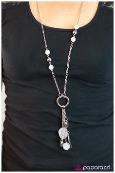 Hanging By A Moment ~ Alternating white and metallic silver beads adorn a silver chain with a centered silver ring at the bottom. A cluster of charms hang from the radiating silver ring in an indigenous style. Charms include a textured leaf, two polished rock beads in a swirled cloud of white, a textured heart, and a heart with a sun etched into its finish.