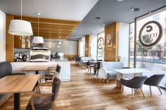 This contemporary cafe in Poland uses a color palette of wood, wood, and grays.