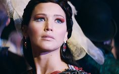 """This links to an article about Covergirl releasing a """"Catching Fire"""" line of makeup. This marketing move ignores the actual content of the film and focuses on beautifying women. (critique)"""