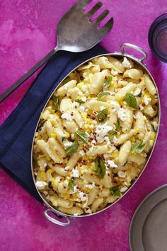 Creamy Corn Mac and Cheese  Serves 6 10 ounces medium-sized dry pasta shells 2 tablespoons butter 2 cups corn kernels 1/4 cup heavy cream 1 cup torn fresh basil leaves, divided 1/2 cup freshly crumbled feta cheese (preferably French or Bulgarian), divided Red pepper flakes Salt